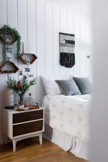 Bedroom with white walls, white bed, and plants