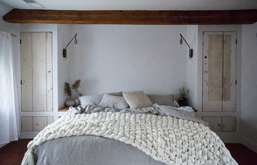 Scandinavian bedroom idea with Chunky knit blanket, wood closet doors, exposed bulb sconces