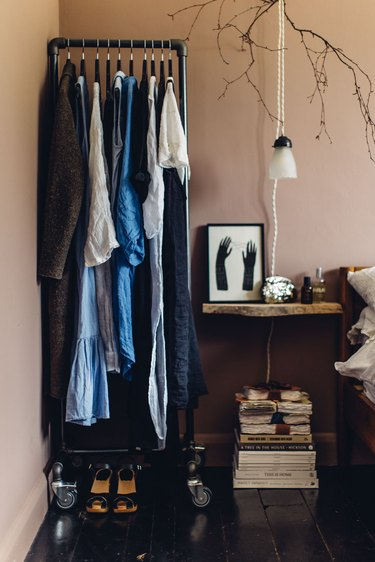 Bedroom storage idea with clothing rack next to bedside table