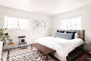 Bedroom with art on the wall and patterned rug.