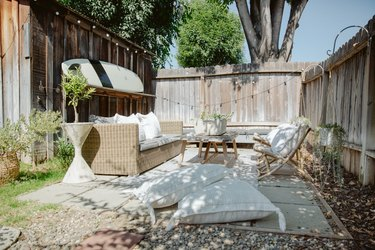 Outdoor idea for small patio design with fence, cement blocks, surfboard, and natural patio furniture