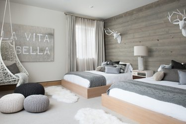 Scandinavian bedroom idea with wood feature wall in a ski cabin room with two beds and woven floor poufs and faux fur rugs