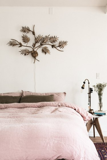 Bedroom with blush colored bedspread and brass artwork on wall