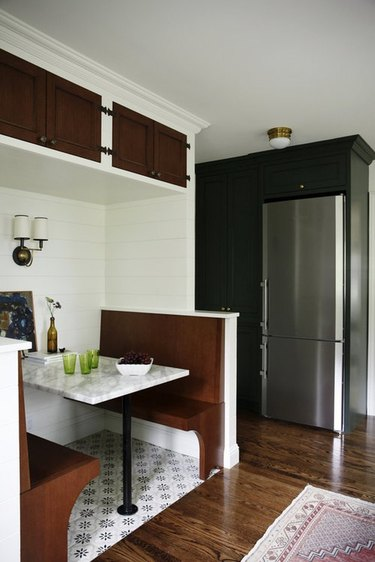 narrow stainless steel kitchen appliances with green kitchen cabinets and built in banquette dining area