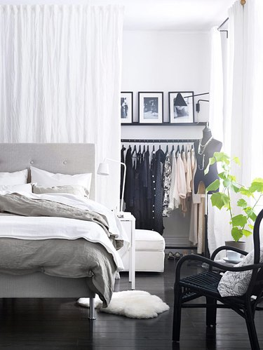 bedroom storage idea makeshift closet using a curtain and clothing rack