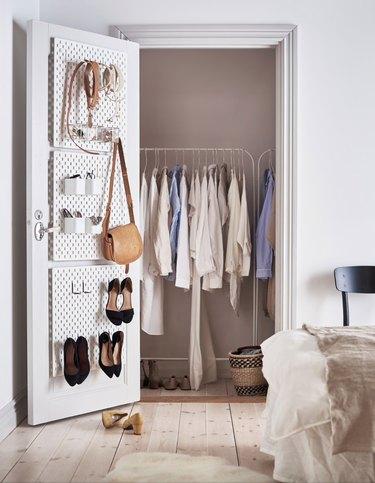 bedroom closet storage idea with shoe rack on door and clothes rack