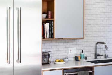 undermount kitchen sink and kitchen faucet with white countertops and cabinets and subway tile backsplash