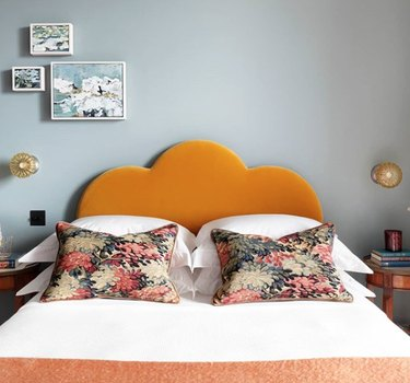 Scandinavian bedroom idea with Orange scalloped velvet headboard with bluish-gray walls and wall sconces