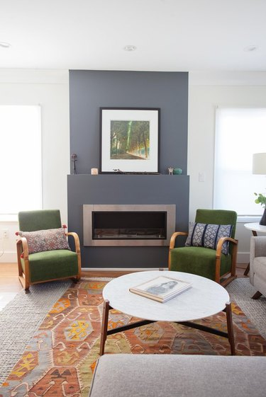 living room space in craftsman home with gray fireplace and green chairs