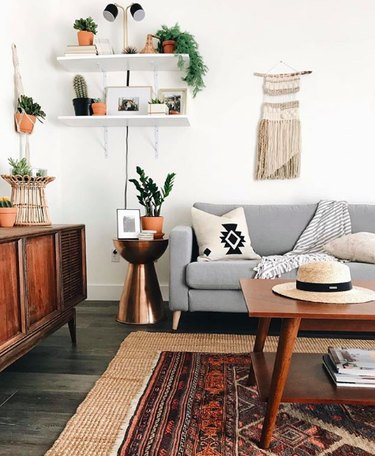 Southwestern-boho living room corner with gray mid-century couch and wooden mid-century coffee table, plus red persian rug layered atop jute rug