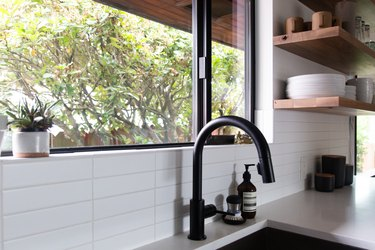 undermount kitchen sink and gooseneck kitchen faucet with white countertops and subway tile backsplash