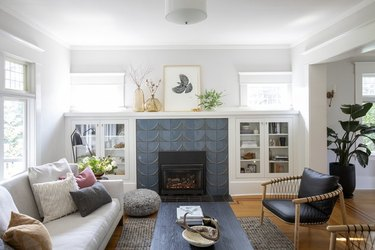 tiled Craftsman style fireplace in living room surrounded by white cabinets