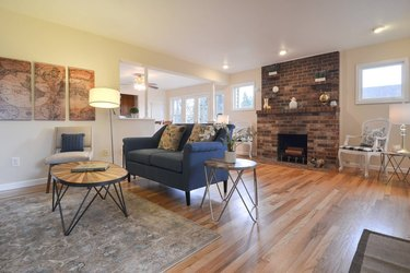 living room space in Craftsman home with brick fireplace
