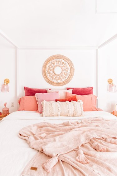 rattan wall hanging in pink and white bedroom