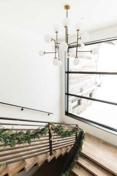 evergreen garland along modern mountain home staircase
