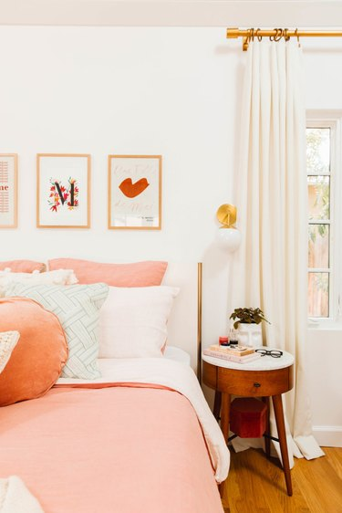 Contemporary bedroom style with pink bedding and floor to ceiling drapery