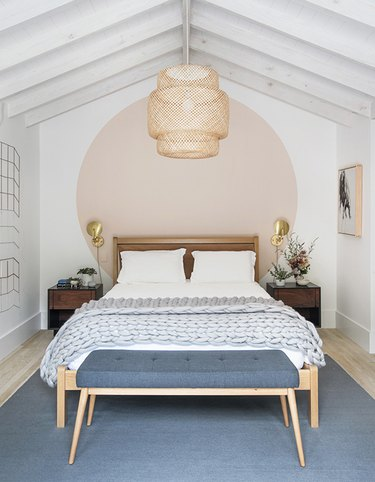 Scandinavian bedroom idea with pink circle accent wall with woven pendant above bed and a pair of sconces on wall