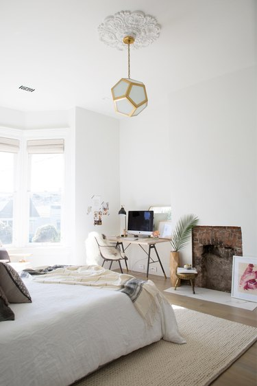 Modern bedroom lighting idea with geometric pendant hanging in the middle of the room