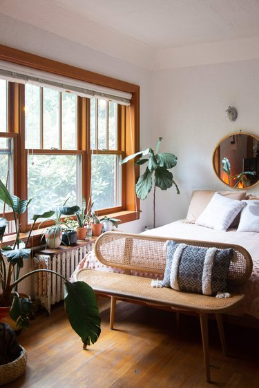 Bed next to large window and natural light