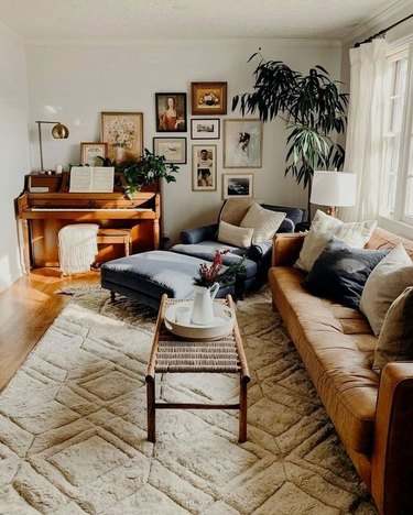 vintage living room style with piano and leather sofa and gallery wall