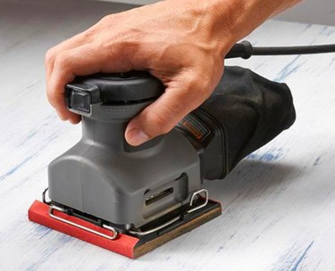 Sanding with a pad sander.