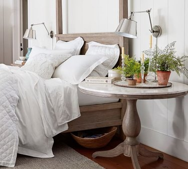 Pottery Barn farmhouse furniture with round bedside table and wood bed frame