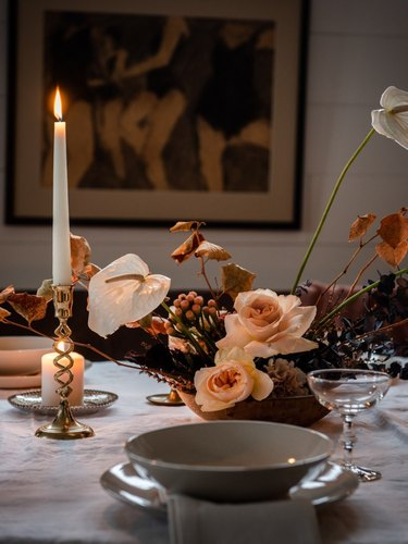 fall floral arrangement with candles on white table
