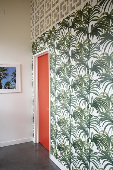 Bright wallpaper with palm design and red door.