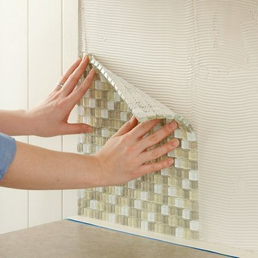 pressing wall tile into mastic