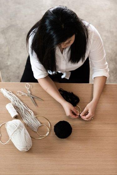woman working on a yarn wall hanging