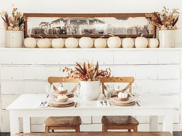 fall floral arrangement on table with mini white pumpkins