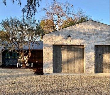 reclaimed wooden garage doors with stone home exterior