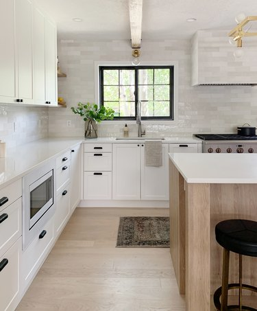 kitchen with white subway tile backsplash and white cabinetry