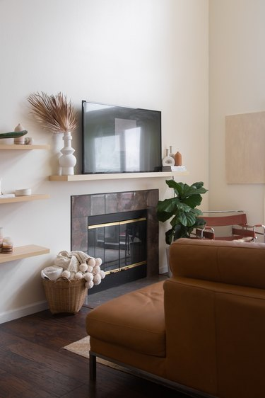living room space with wood shelves, fireplace, and television