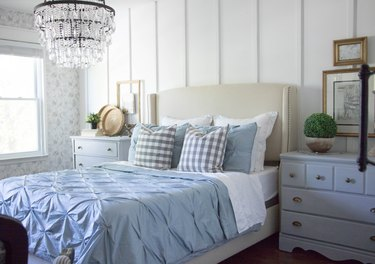 A chandelier hanging above a bed