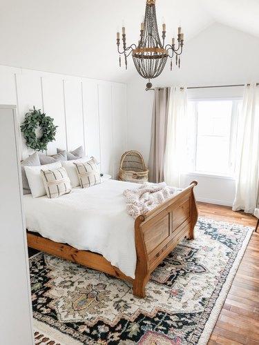candelabra style bedroom chandelier hanging above wood frame bed