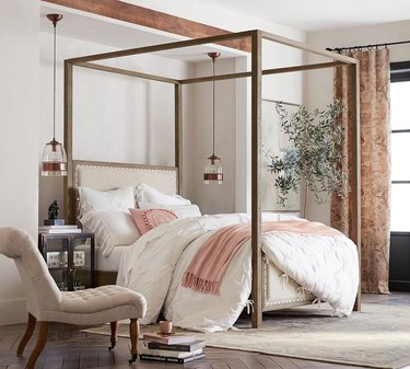 glass pendants hanging either side of timber frame canopy bed