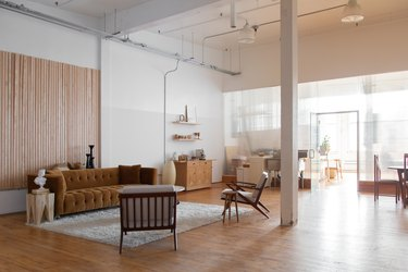 office space with white walls, mustard couch and wood chairs