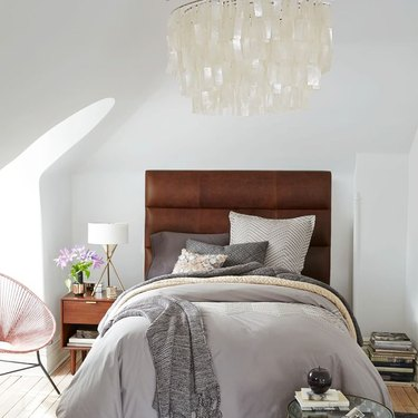 bedroom chandelier hanging above bed with leather upholstered headboard