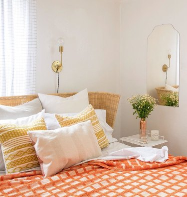 industrial wall sconce with orange and yellow bedroom and cane headboard
