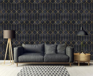living room space with black couch and black and gold geometric wallpaper in the background