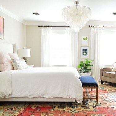 neutral bedroom color idea with  capiz chandelier and bold patterned rug