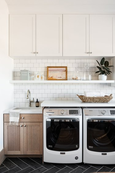 Garage Laundry Room with Front load washer dryer, cupboards, subway tile, white shelf, white cupboard, natural wood sink area.
