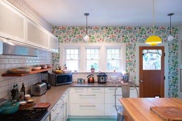kitchen with floral wallpaper and subway tile backsplash