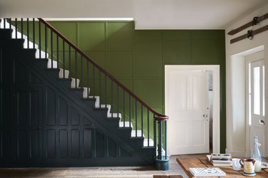 Green wall and black staircase with white door