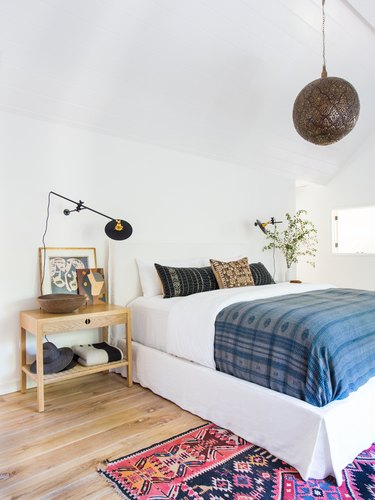 bohemian bedroom lighting idea with articulating wall lamp and pendant over bed