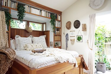 small bohemian bedroom with built-in open shelving and wood bed frame