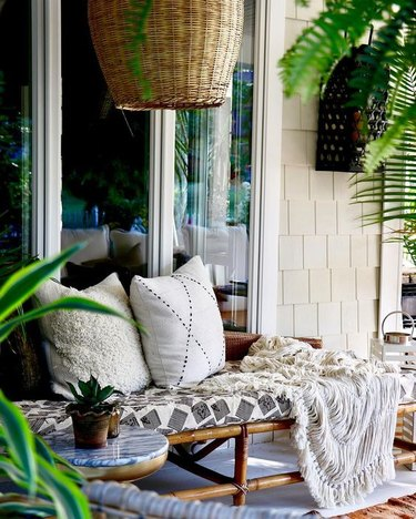 rattan daybed with accent pillows and throw blanket