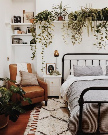 bohemian bedroom with lush greenery and leather lounge chair