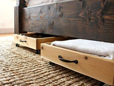 Cedar rolling drawers beneath a bed